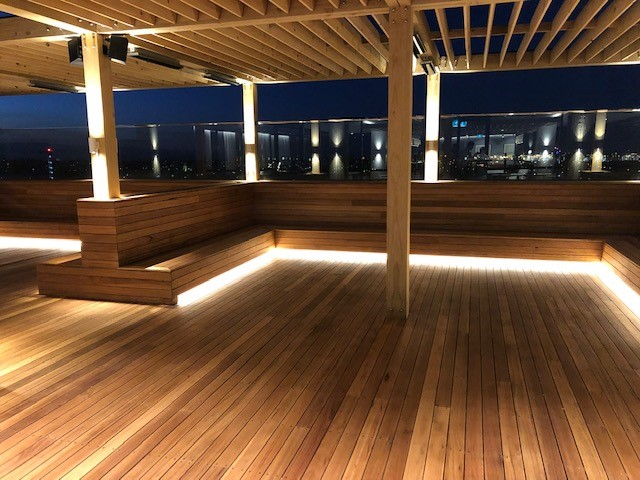 A wooden seating area with backlighting installed