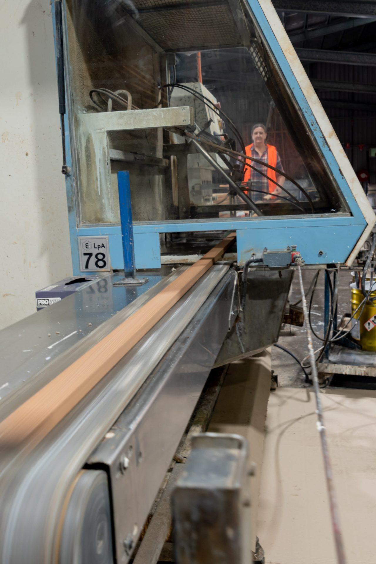A woodworker running wood through a machine